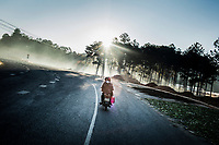 A motorbike drives along a highway through PES protected forests in Lam Dong province, in central Vietnam.
