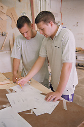 Manager discussing template for product with wood machinist,