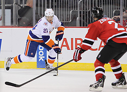 Mar 8; Newark, NJ, USA; New York Islanders right wing Kyle Okposo (21) skates with the puck while being defended by New Jersey Devils defenseman Marek Zidlicky (2) during the first period at the Prudential Center.