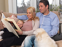 Happy family and a dog enjoying their time together at home. Pregnant mother, daddy and their daughter watching a photo album.