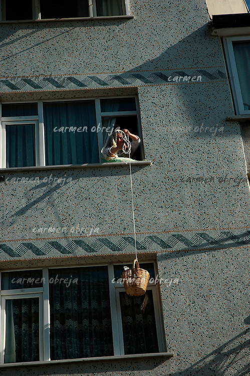a woman lowers a basket on strings from  her window to receive some goods in the asian part of Istanbul