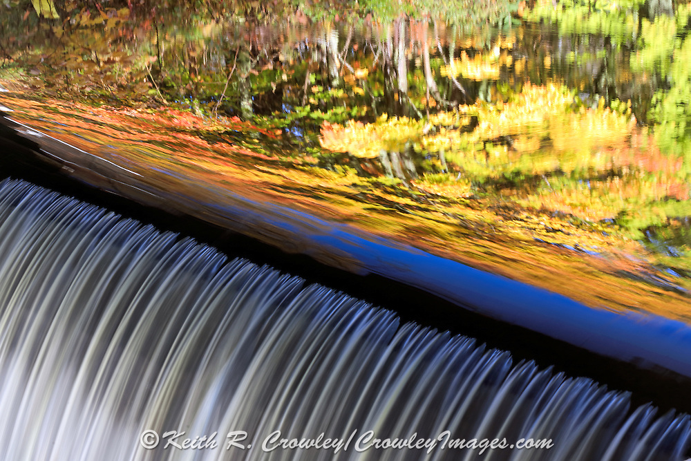 Water cascades over a roller dam on the Eau Claire River with vivid fall colors reflecting in southern Bayfield County, Wisconsin