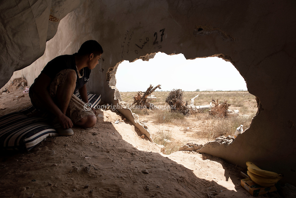Libya: a fighter sympathising with Libya's Government of National Accord's (GNA) is seen nearby a hole in a surrounding wall  used to check ISIS positions in Ouagadougou conference center. Alessio Romenzi