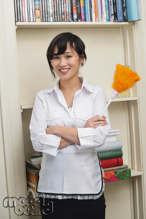 Portrait of female housecleaner holding feather duster