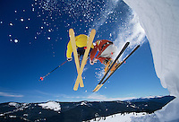 Skiers launching off snow bank Hitting the Slopes low angle view