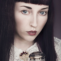 Young female with dark hair, blue eyes, pale skin wearing a white lace top, holding a glass pot looking at the camera.