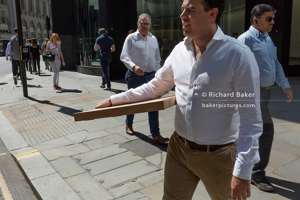 A man carries a pizza takeaway box level on Threadneedle Street during the 2018 heatwave in the City of London, the capital's historic financial district, on 2nd August 2018, in London, England.