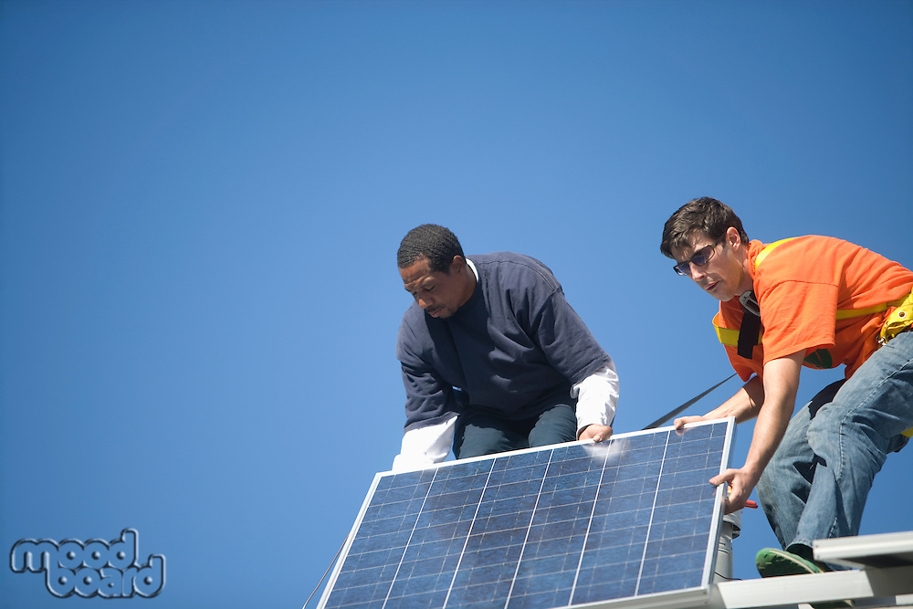 Two men lifting a large solar panel