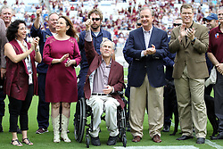 Texas Governor Greg Abbott, with Texas A&M chancellor John Sharp, right, gives a Texas A&M Gig'Em symbol at Kyle Field in College Station, Texas before the start of an NCAA college football game between Prairie View A&M and Texas A&M Saturday, Sept. 10, 2016, in College Station, Texas. (AP Photo/Sam Craft)