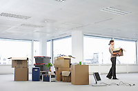 Office worker carrying carton near cartons and equipment on floor of empty office space