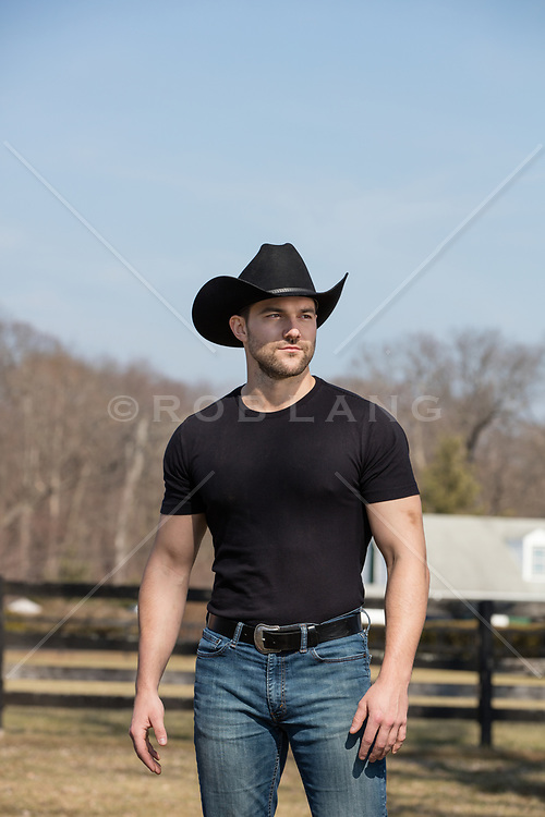 muscular good looking cowboy on a rustic ranch