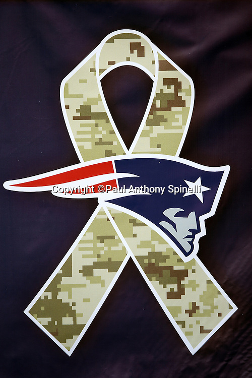 A sideline banner is decorated with an NFL logo intertwined with a military logo as part of the Salute to Service initiative before the New England Patriots 2015 week 9 regular season NFL football game against the Washington Redskins on Sunday, Nov. 8, 2015 in Foxborough, Mass. The Patriots won the game 27-10. (©Paul Anthony Spinelli)