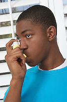Young man using asthma inhaler