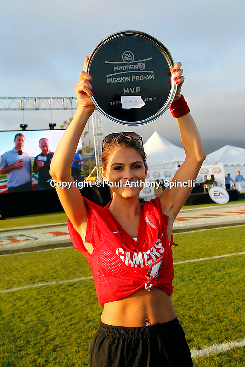 Actress Maria Menounos (12) of the Gamers team celebrates winning the Most Valuable Player Award after playing flag football in the EA Sports Madden NFL 11 Launch celebrity and NFL player flag football game held at Malibu Bluffs State Park on July 22, 2010 in Malibu, California. (©Paul Anthony Spinelli)
