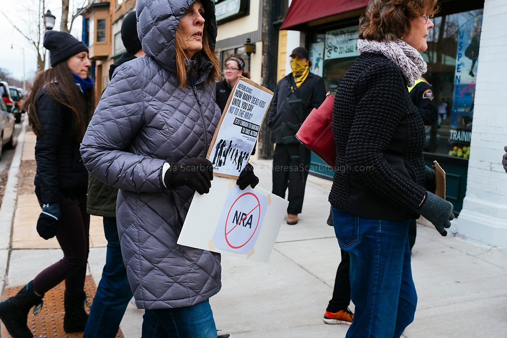Janesville, Wisconsin, USA. 24th March, 2018. Protesters march to Congressman Paul Ryan's, Speaker of the House, office building in Janesville, Wisconsin's March for Our Lives event. In the background counter protesters stood silently, one man dressed in all black with an assault rifle.