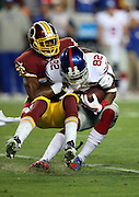 New York Giants wide receiver Rueben Randle (82) gets tackled by Washington Redskins strong safety Bashaud Breeland (26) after catching a first quarter pass on the first play from scrimmage during the NFL week 4 regular season football game against the Washington Redskins on Thursday, Sept. 25, 2014 in Landover, Md. The Giants won the game 45-14. ©Paul Anthony Spinelli