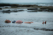 Pregnant woman floating on her back in a tide pool by the sea