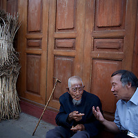 Two local men chat in the evening in Heshun.