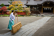 Before Futarasan Shrine opens, a man dressed in traditional clothing (gi and hakama) uses a giant straw broom to sweep the  front of the shrine.