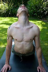 Portrait of young man in the upward facing dog pose of yoga