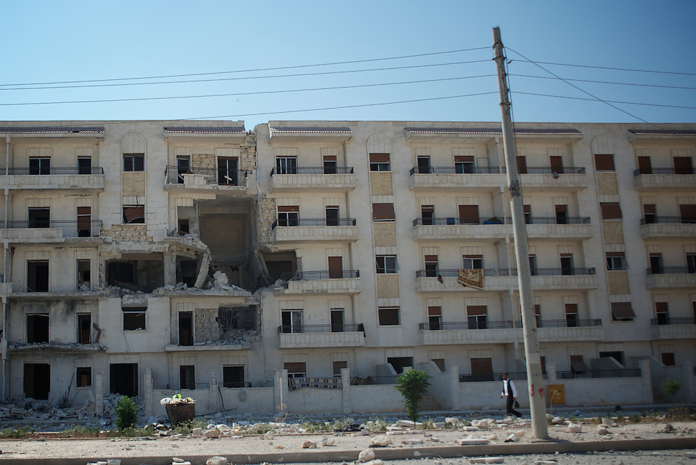 August 09, 2012 - Aleppo, Syria: A man passes by a destroyed faced of a residential building in Aleppo's Haneno neighborhood...The Syrian army and the FSA have in the past week exchanged heavy fire in a battle for the control of Syria's economic capital, Aleppo. (Paulo Nunes dos Santos/Polaris)