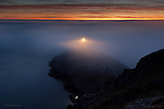 Rays of light from South Stack lighthouse, Holy Island, Anglesey, under a thick bank of fog at sunset, caused by a second day of temperature inversion over North Wales and here over the Irish Sea. Fishermen's torches light the rocks at the base of the cliffs in the blue gloom.