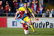 Scunthorpe United forward George Thomas (18) shields the ball from Wimbledon defender Rod McDonald (26)  during the EFL Sky Bet League 1 match between Scunthorpe United and AFC Wimbledon at Glanford Park, Scunthorpe, England on 30 March 2019.