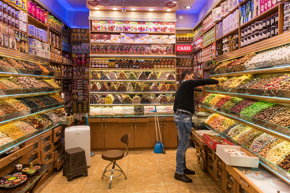 Adult male restocking some bins inside of sweet and dried goods shop located in Istanbul Spice bazaar in Turkey