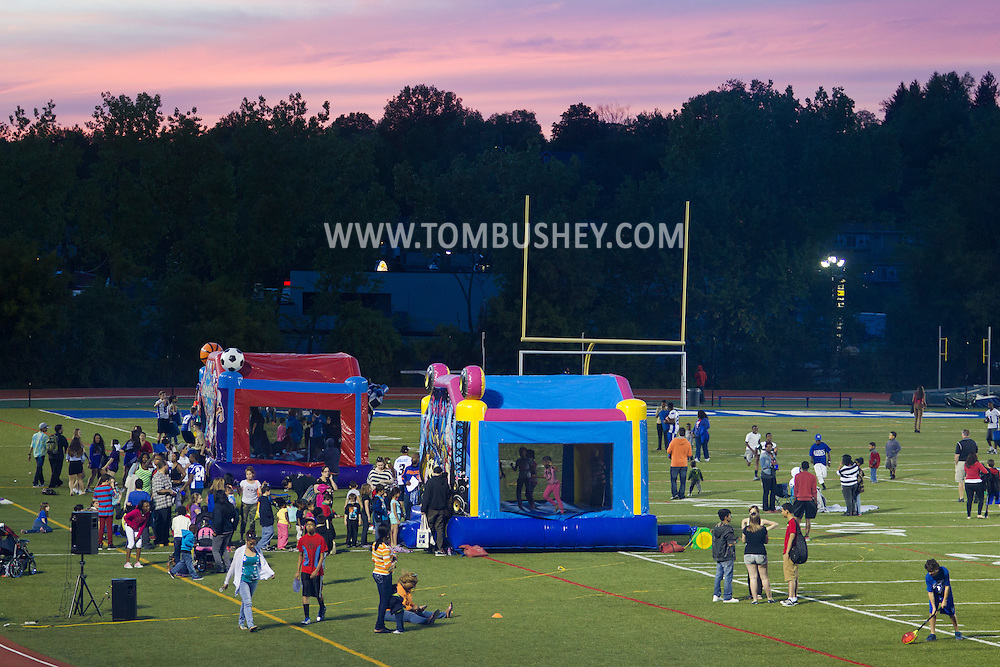 Middletown, New York - Children play games with Middletown High School varsity athletes at Faller Stadium during Family Fun Night on May 17, 2013.