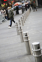 January 3, 2018 - New York, New York, U.S. - Pedestrians walk past metal bollards at Times Square in New York. New York city plans to install 1,500 new security barriers in high-profile locations to guard against vehicle attacks and other terror-related incidents. Mayor de Blasio announced the plan at a press conference held in Times Square on Tuesday. He said the metal bollards will replace some of the concrete cubes and barriers that have been placed as temporary measures near pedestrian areas. (Credit Image: © Wang Ying/Xinhua via ZUMA Wire)