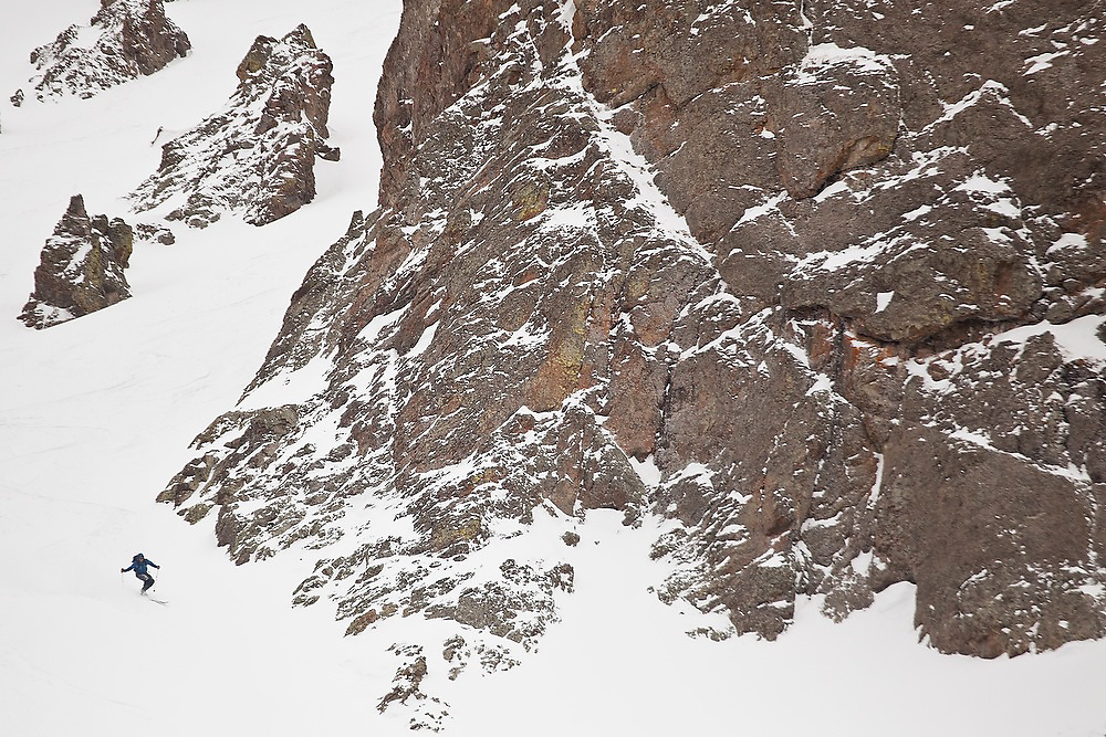 Backcountry skier Sterling Roop catches turns below a headwall of Hayden Peak, San Juan Mountains, Colorado.