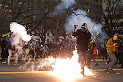 WASHINGTON, USA - January 20: A flash grenade explodes at the feet of an Anti-Trump protestor after protestors set a limousine on fire during clashes with police after President Trump was sworn into office in Washington, USA on January 20, 2017.