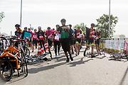 De koeriers rennen naar hun fiets bij de start. In Nieuwegein wordt het NK Fietskoerieren gehouden. Fietskoeriers uit Nederland strijden om de titel door op een parcours het snelst zoveel mogelijk stempels te halen en lading weg te brengen. Daarbij moeten ze een slimme route kiezen.<br /> <br /> Start of the races. In Nieuwegein bike messengers battle for the Open Dutch Bicycle Messenger Championship.