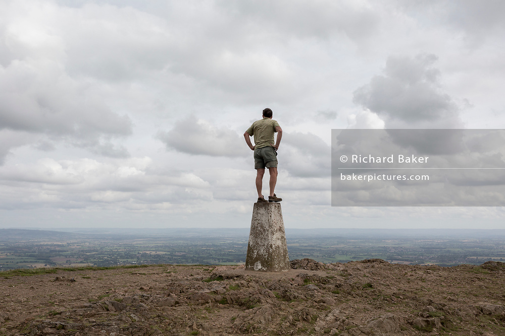 A hill climber stands on the top of the trig-point and looks across distant landscapes from the top of The Beacon, on 15th September 2018, in Malvern, Worcestershire, England UK. Worcestershire Beacon, also popularly known as Worcester Beacon, or locally simply as The Beacon, is a hill whose summit at 425 metres (1,394 ft)[1] is the highest point of the range of Malvern Hills that runs about 13 kilometres (8.1 mi) north-south along the Herefordshire-Worcestershire border, although Worcestershire Beacon itself lies entirely within Worcestershire. A triangulation station, also known as a triangulation pillar, trigonometrical station, trigonometrical point, trig station, trig beacon, or trig point, and sometimes informally as a trig, is a fixed surveying station, used in geodetic surveying and other surveying projects in its vicinity.