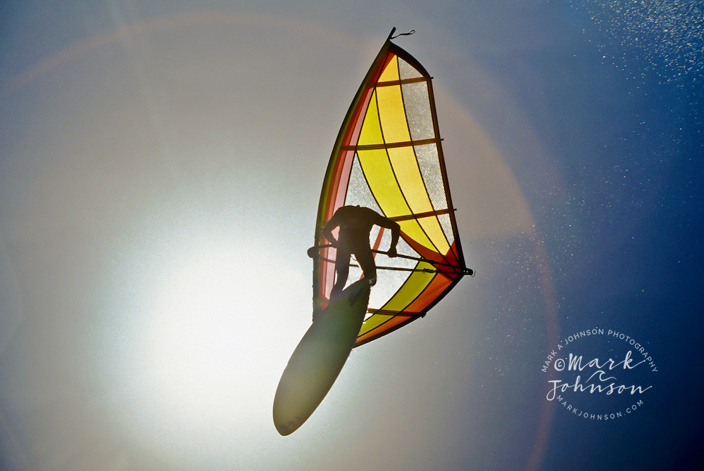 Airborne windsurfer siluotted against the sun in Hawaii
