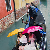 VENICE, ITALY - JUNE 07:   Tourists on a gondola try to find someto find some repair from heavy rain using colourful umbrellas on June 7, 2011 in Venice, Italy. Thunderstorms and heavy rain have hit Venice causing an out season high tide of 90 cm flooding St Mark's square.