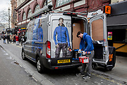 An employee with Fallon & Co. wearing identical work top uniform as the male on the rear of his company's parked van, gathers tols and materials including Soldalit, an exteriors water repellent paint, on 17th February 2020, in London, England. Fallon & Co is  a privately owned business with over 25 years experience servicing clients in the Domestic, Commercial & Industrial sectors.