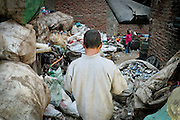 Collected garbage are thrown in an open outdoor area to be filtered and sorted. Ezbet El Nakhl, 2009