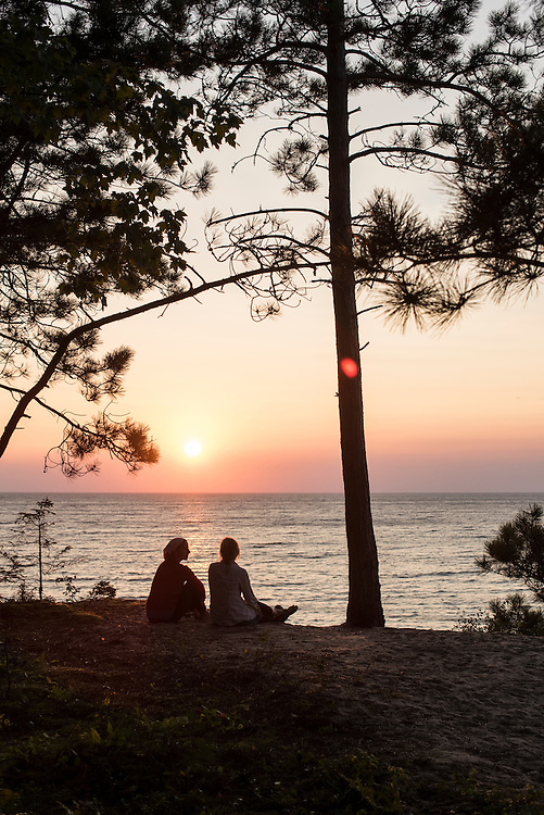 Friends enjoy a sunset over Lake Superior form atop a sand dune at Pictured Rocks National Lakeshore near Munising, Michigan.