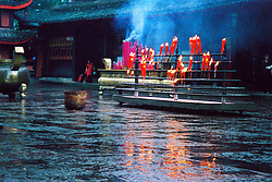 China, Sichuan, 2007. Fire and water exists side by side in this rainy temple scene halfway up Emei Shan, a mountain range famous for its cloud forest atmosphere..