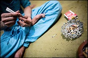 "Kastouri,  a transvestite of 16 years, prepares a couple of cigaretttes with hashish. He lives in a common petty apartment with other friends, most of them transvestites, that he considers his new family. Evening in Lahore, Pakistan on Monday, December 01 2008.....""Not men nor women"". Just Hijira, Kusra. Painted lips, Kajal surrounding their eyes and colourful veils..Pakistan is today considered a strongly, foundamentalist as well, islamic country. But under its reputation, above all over the talebans' continuos advancing, stirs a completely extraneous world, a multiethnic mixed society. Transvestites make part of it, despite this would not be admitted by a strict law. Third gender, the Hijira are born as men (often ermaphrodites) or with an ambiguous genital situation, and they have their testicles and penis removed through a - often brutal - surgical operation. The peculiarity is that this operation does not contemplate the reconstruction of a female organ. This is the reason why they are not considered as men nor women, just Hijira. They are often discriminated, persecuted  and taxed with being men prostitutes in the muslim areas. The members of this chast perform dances during celebrations, especially during weddings, since it is anciently believed that an EUNUCO's dance and kiss in the wedding day brings good luck to the couple's fertility...To protect the identities of the recorded subjects names and specific .places are fictionals."