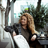 Young blonde woman taking a break at a coffee bar. Smiling and watching away from camera.