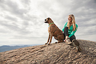 Young woman and dog sitting on a summit