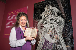 © Licensed to London News Pictures. 16/04/2018. Winchcombe, Gloucestershire, UK. Sudeley Castle's 'Royal Sudeley 1,000, Trials, Triumphs and Treasures'. Picture of LADY ASHCOMBE who lives at the castle, holding a book with wife of Henry VIII Katherine Parr's formal signature beside life-size glass-engraved portrait of Katherine Parr by critically acclaimed artist, John Hutton. Treasures from Sudeley Castle's 1,000 year history have gone on show in a new exhibition. Called 'Royal Sudeley 1,000, Trials, Triumphs and Treasures', the newly refurbished exhibition includes a collection of priceless objects and curiosities. The exhibition includes a one-of-a-kind, life-size glass-engraved portrait of Katherine Parr by critically acclaimed artist, John Hutton. The artwork was re-discovered during the refurbishment of a holiday cottage on the estate, where it had been for decades. Its importance has now been realised and so it has been brought into the exhibition collection. Numerous items of historic significance are also on display, such as a lock of Katherine Parr's hair, her prayer book and an intricate lace christening canopy believed to have been worked on by Anne Boleyn for the christening of her daughter, Elizabeth I. Sudeley was a royal residence, closely associated with some of the most famous English monarchs, including Edward IV, Richard III, Henry VIII, Lady Jane Grey, Katherine Parr, Elizabeth I and Charles I. The Castle was even home to a secret Queen of England, Eleanor Boteler, whose royal status was unknown for centuries. Photo credit: Simon Chapman/LNP