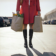 woman standing in grocery store parking lot holding bags with groceries.