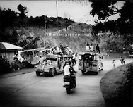 21..Jeepneys, piled high with passengers, pass each other outside Coron Town, Busuanga Island, Philippines.
