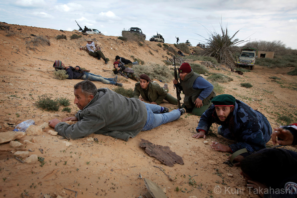 Rebel soldiers against Col. Muammar Gaddafi lay on the ground to take cover from shells dropped by the government force near Ras Lanuf on March 9, 2011. The government military and rebels kept fighting for taking control of the town for the last two days. .Photo by Kuni Takahashi