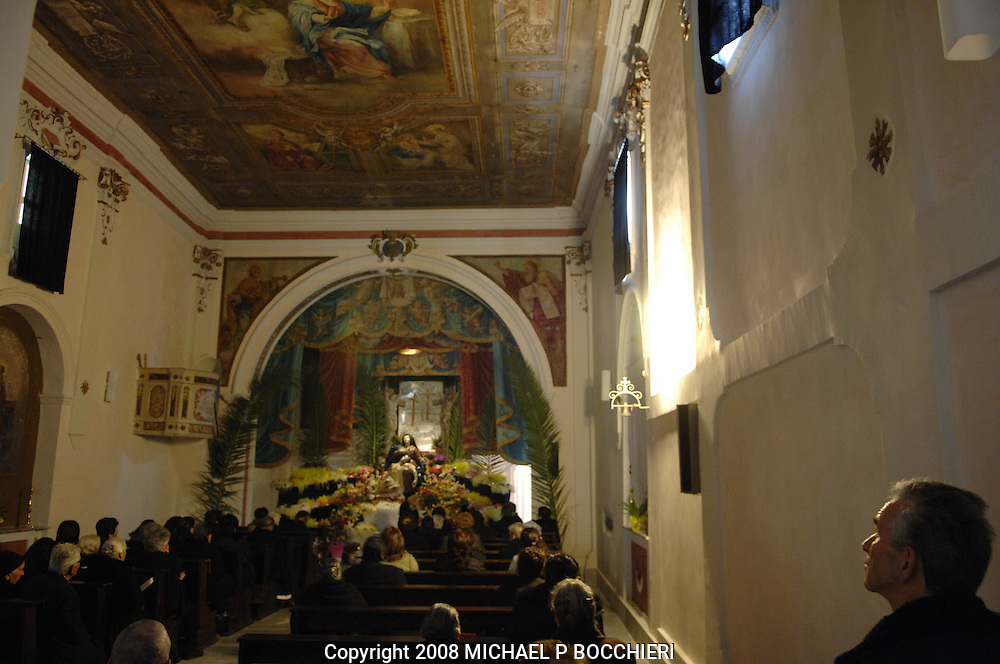 NOCERA TIRINESE, ITALY - MARCH 20:  People pray to the shrine of La Madonna at the Chiesa dell' Annuziata days before the Rito Dei Battienti (rite of the beaters)  March 20, 2008 in Nocera Tirinese, Calabria, Italy. A yearly Easter ritual dating back to the mid-13th century the Processione della Addolorata (procession of the Golden Madonna) and Rito dei Battienti (rite of the beaters) includes devote Catholics that flagellant themselves in the streets and jog the route of the Easter procession, enduring the pain and suffering of religious sacrifice in the name of spiritual cleansing. (Photo by Michael Bocchieri/Bocchieri Archive)..