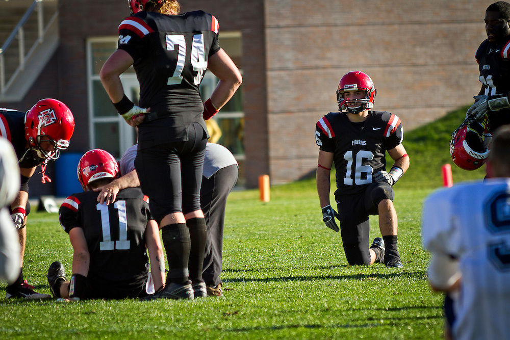 Kelsey Davis '12, right, drops to a knee and looks on after quarterback Mike McCabe '13 (#11) took a nasty hit during Saturday's victory over Illinois College.
