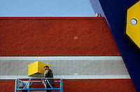 JEROME A. POLLOS/Press..Bert Bozarth cleans light fixtures on the wall of Best Buy from a lift on Monday.